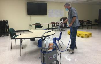 Man using machine to sanitize, disinfect furniture.