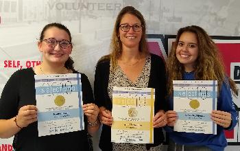 New Richmond HS seniors Emma Lewin and Makaylee High-key  with teacher Amy Hauserman.