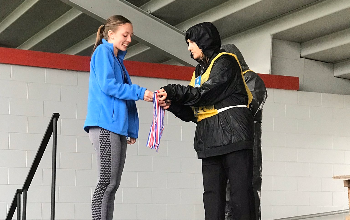 Jenna Burns receives her medal for an eighth-place finish in the cross country regional meet.
