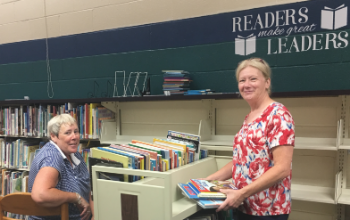 Betsy Groen and Becky Walriven organize books at Monroe Elementary School.