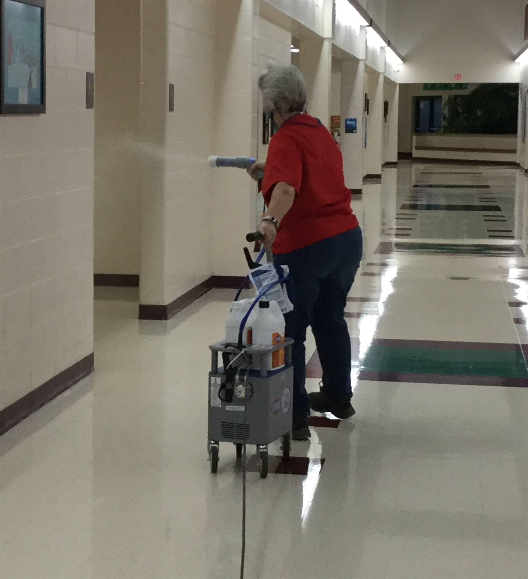 Custodian sanitizing main hallway