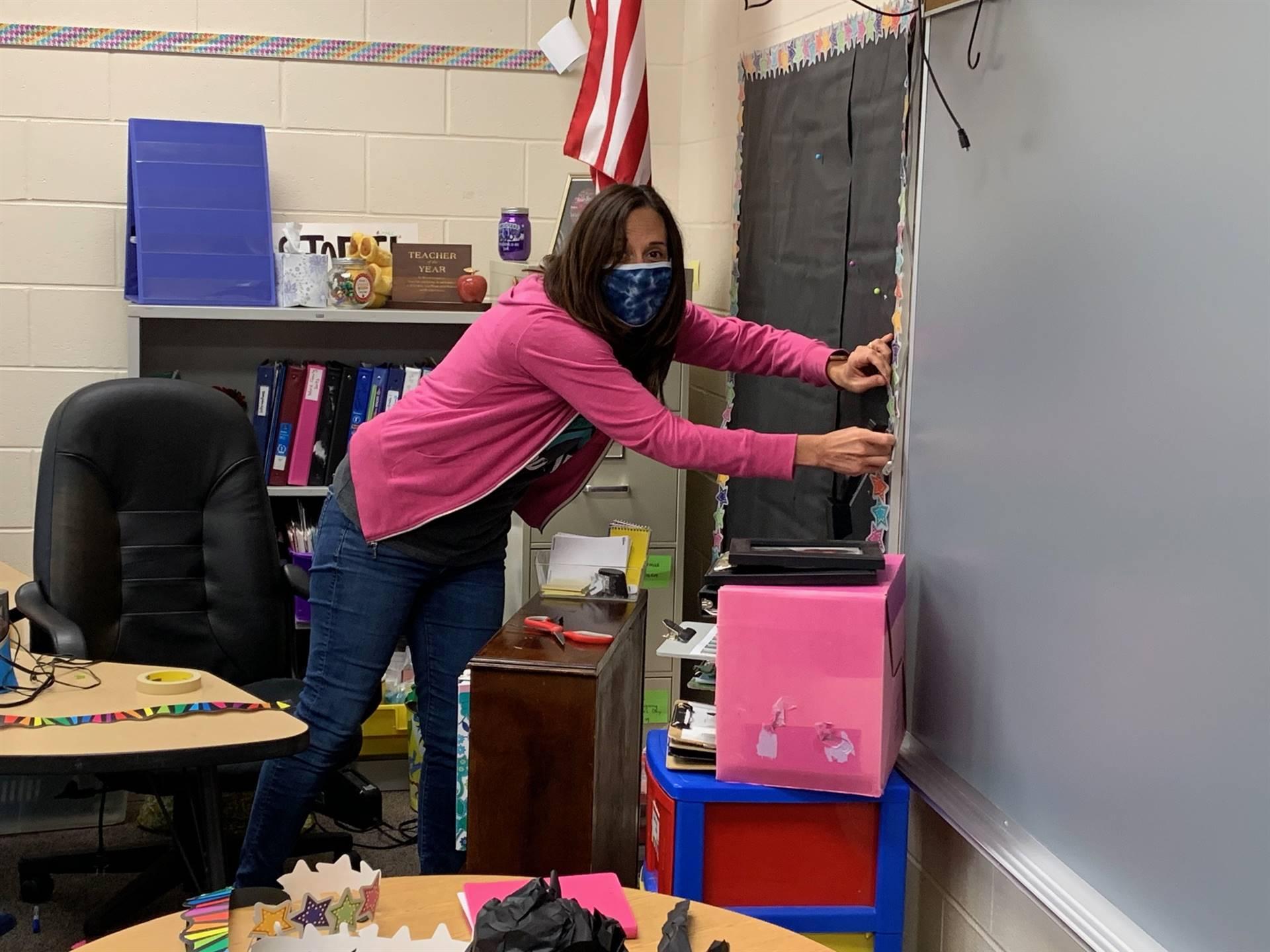 Teacher working on bulletin board