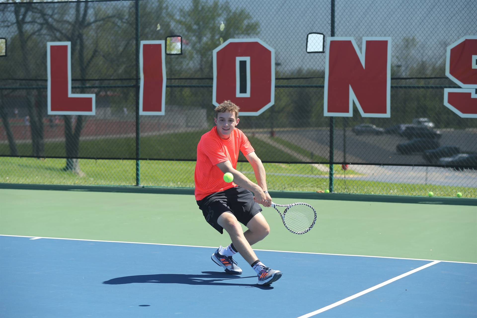 boys tennis player about to hit ball
