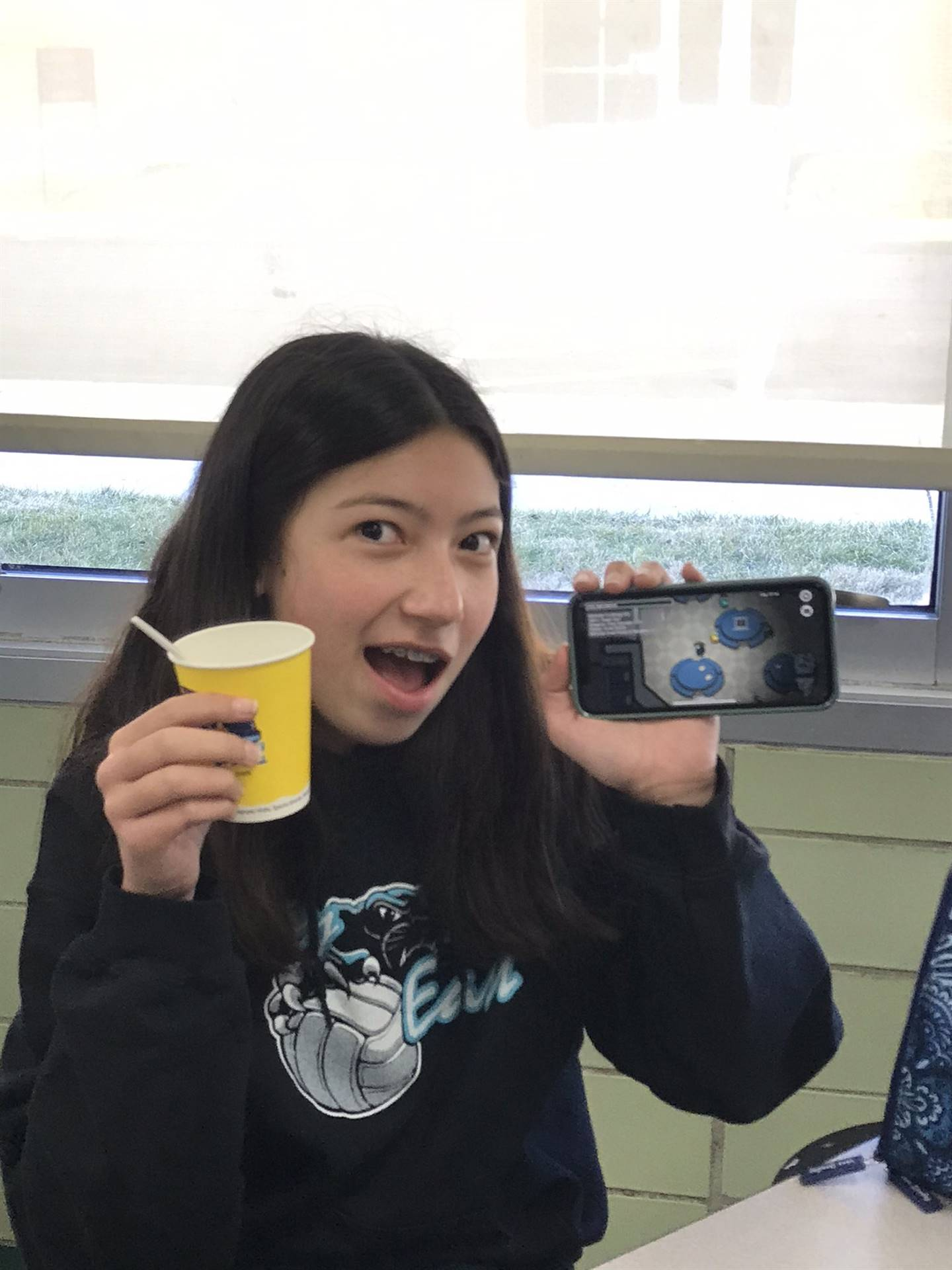 Student with slushie and phone