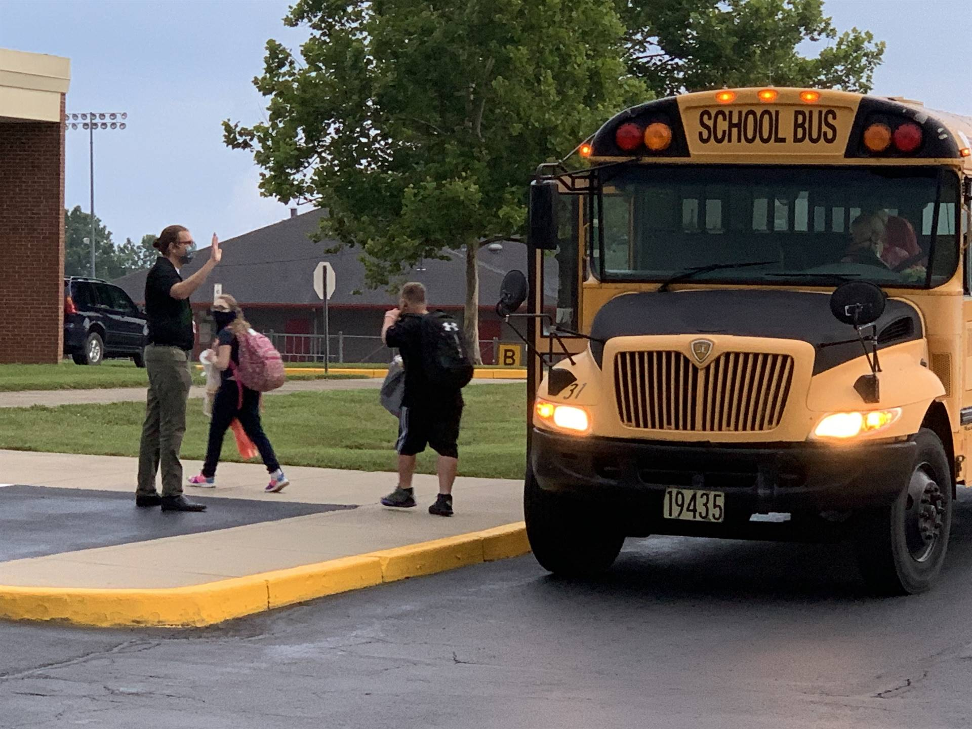 Teacher greets students exiting the bus